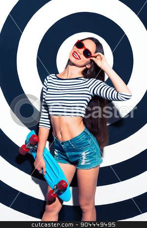 Creative concept of beautiful sexy girl stock photo, Colorful picture of beautiful slim young woman with long hair on black and white background. Girl with sunglasses looking at camera, cheerfully smiling and holding skateboard by Dmytro Sidelnikov