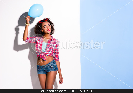 Creative concept of beautiful sexy girl stock photo, Colorful picture of beautiful slim young woman with curly hair on white and blue background.  Girl with red sunglasses smiling and holding blue baloon by Dmytro Sidelnikov