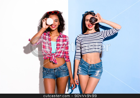 Funky couple. Creative concept of beautiful sexy girls stock photo, Colorful picture of beautiful slim young women on white and blue background. Girls smiling and holding donuts by Dmytro Sidelnikov