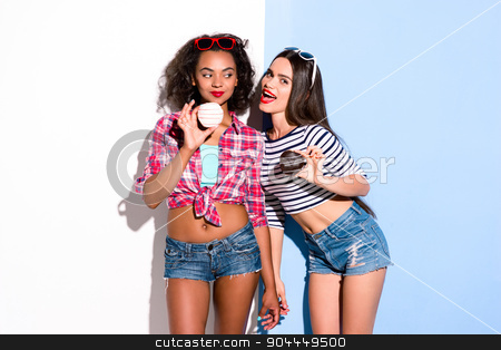Funky couple. Creative concept of beautiful sexy girls.  stock photo, Colorful picture of beautiful slim young women on white and blue background. Girls holding donuts. One girl trying to bite friend's donut by Dmytro Sidelnikov