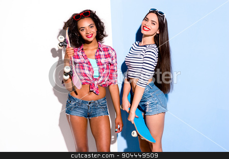 Funky couple. Creative concept of beautiful sexy girls.  stock photo, Colorful picture of beautiful slim young women on white and blue background. Girls cheerfully smiling and holding  skateboards by Dmytro Sidelnikov
