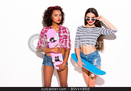 Funky couple. Creative concept of beautiful sexy girls.  stock photo, Colorful picture of beautiful slim young women on white background. Girls smiling and holding skateboards by Dmytro Sidelnikov