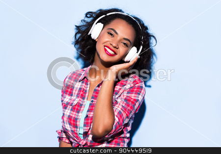 Creative concept of beautiful sexy girl stock photo, Colorful picture of beautiful slim young woman with curly hair on white background. Girl with headphones smiling and listening to music with her eyes closed by Dmytro Sidelnikov