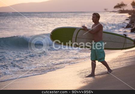 Surfer Walking Surfboard to Water stock photo, Adult surfer walking surfboard toward ocean waves by Scott Griessel