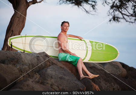 Man Sitting with Surfboard stock photo, Single adult surfer male outdoors sitting with surfboard on rocks by Scott Griessel