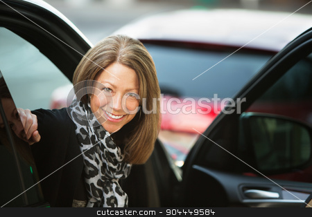 Happy Woman in Urban Scene stock photo, Beautiful smiling adult business woman in car with open door by Scott Griessel