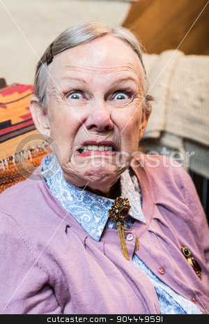 Old Woman Making a Face stock photo, Woman making a scary face at the camera by Scott Griessel
