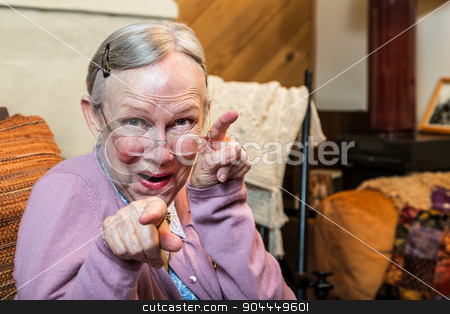 Old Woman in Living Room Dancing stock photo, Funny old woman in pink sweater showing dance style hand gesture by Scott Griessel