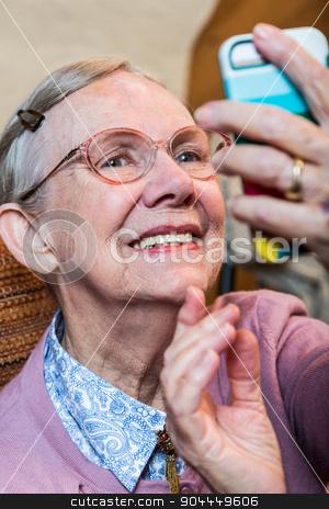 Happy Old Woman Taking Selfie stock photo, Happy old woman in pink sweater taking a smiling selfie by Scott Griessel