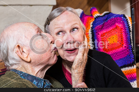 Elderly Gentleman Kissing Elderly Woman on Cheek stock photo, Elderly gentleman kissing woman on cheek in indoors by Scott Griessel