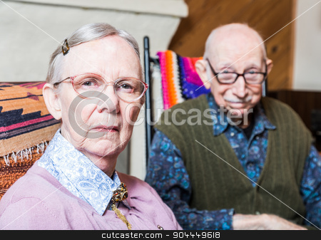 Old Woman and Man Sitting in Livingroom stock photo, Old woman and man looking at camera skeptically by Scott Griessel