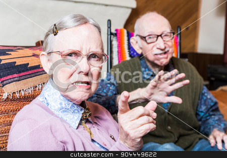 Angry Couple stock photo, Angry old man and woman scowling at camera sitting in livingroom by Scott Griessel