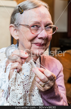 Smiling Elderly Woman with Crochet stock photo, Elderly woman in pink sweater crocheting with demure smile by Scott Griessel