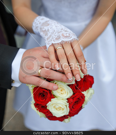 hands of the bride and groom with rings stock photo, hands of the bride and groom with rings on a beautiful wedding bouquet by timonko