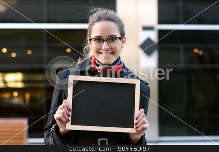 Business woman holding a chalkboard. stock photo, Business woman holding a chalkboard outside her office. Copyspace. by nicolas menijes