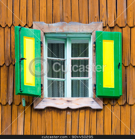 Colorful vintage wooden window shutters. stock photo, Decorative, green yellow, vintage, window shutters on a brown wooden wall. Retro detail from traditional alpine mountain house with wooden paneling. Austria, Germany, Slovenia. Square composition. by kasto