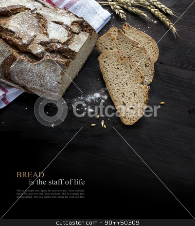 Rustic bread loaf and slices on dark wood fading to black, sampl stock photo, Rustic crusty bread loaf and slices with some wheat ears on dark wood, background is fading to black, sample text Bread is the staff of live. Concept image for a bakery, equally suitable for charities for famine relief. by Maren Winter