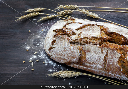 rustic bread and wheat on a dark wooden table stock photo, rustic crusty bread and wheat ears on a dark wooden table by Maren Winter