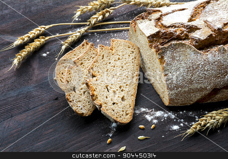 rustic loaf of bread and slices with wheat on dark wood stock photo, rustic crusty loaf of bread and slices with wheat ears on a dark wooden table, copy space, selected focus by Maren Winter