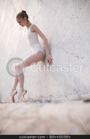 Slim dancer stands in a ballet pose stock photo, Slim dancer stands in a ballet pose and looking down on a gray urban concrete background. Outdoors shooting with sun light. by bezikus