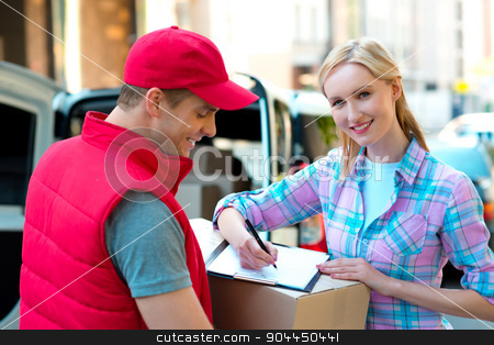Sign here please! Smiling young delivery man holding a cardboard box while beautiful young woman putting signature in clipboard stock photo, Colorful picture of courier delivers package for woman. Woman is receiving the parcel and smiling.   by Dmytro Sidelnikov