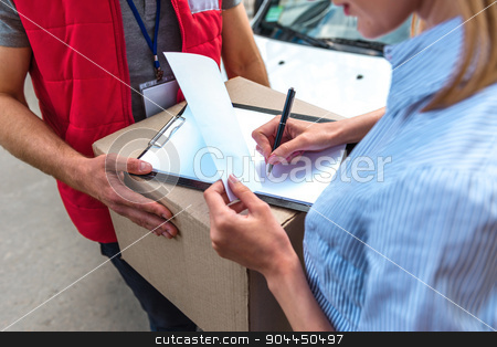 Concept of courier delivers package for woman stock photo, Colorful picture of courier delivers package for woman. Courier is giving the woman a box. Woman is signing the dokument and smiling.   by Dmytro Sidelnikov