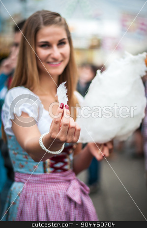 Attractive young woman wearing a traditional Dirndl dress with cotton candy floss at the Oktoberfest. stock photo, Beautiful young smiling woman wearing a traditional Dirndl dress with cotton candy floss at the Oktoberfest.  by uleiber