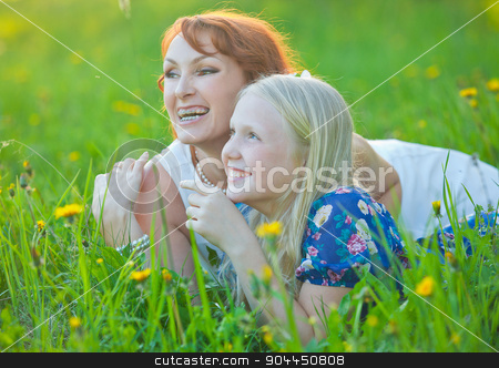 Mom with braces and her little daughter lie on grass smiling at the park stock photo, Portrait of smiling beautiful young woman and her little daughter sitting on grass, against green of summer park. by traza