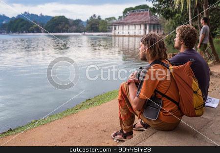 Young Man Traveler with backpack reading book stock photo, Young Man Traveler with backpack reading book and writing notes outdoor mountains on background Summer vacations and Lifestyle concept by Vassiliy Kochetkov