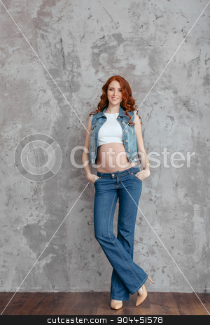 Portrait of the young pregnant woman stock photo, Studio portrait of beautiful slim sexy pregnant woman wearing casual jeans over grunge gray wall  by Dmytro Buianskyi