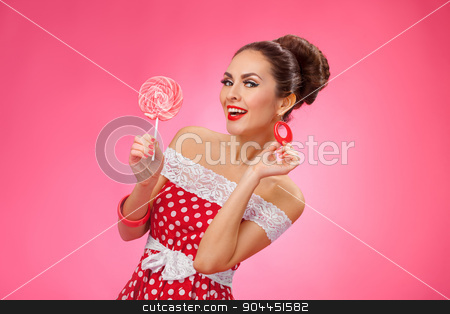 Happy Woman Holding red Lollipop. Pin-up retro style. stock photo, Funny portrait of cute young female model with candy in her arms wearing red dress by Dmytro Buianskyi
