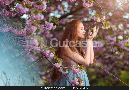 Beautiful pregnant woman in blooming garden stock photo, Beautiful pregnant woman smells blossom, outdoor in nature. by Dmytro Buianskyi