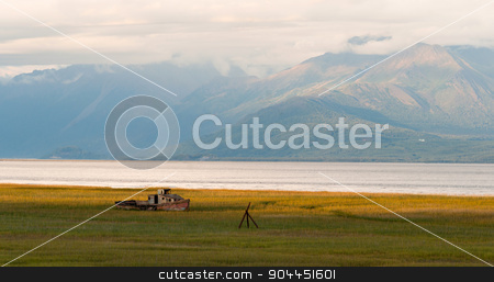 Forgotten Wooden Boat Sits Abandoned Cook Inlet Alaska stock photo, Once a fisherman's dream one day it just flipped and the new permanent moorage is a grassy piece or marsh by Christopher Boswell