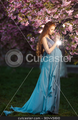 Beautiful pregnant woman in blooming garden stock photo, Beautiful pregnant woman standing among trees, outdoor in nature. by Dmytro Buianskyi
