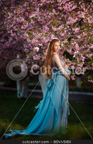 Young  pregnant woman relaxing and enjoying life in nature stock photo, Young beautiful pregnant girl with long brown hair in blue dress by Dmytro Buianskyi