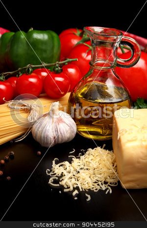 Pasta raw isolated on black with tomatoes,olive oil,garlic horiz stock photo, Long group of raw pasta tied with string isolated on black board with basil,tomatoes and carafe full of olive oil upright by Tadeusz Wejkszo