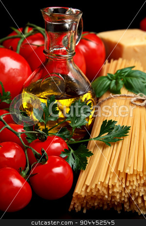 Pasta raw isolated on black with tomatoes,olive oil,garlic verti stock photo, Long group of raw pasta tied with string isolated on black board with basil,tomatoes and carafe full of olive oil upright and cheese by Tadeusz Wejkszo