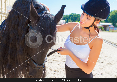 Beautiful horsewoman with a horse stock photo, Portrait of a beautiful horsewoman wearing an equestrian helmet and a white top standing near a big brown horse, looking at the animal  by Zinkevych