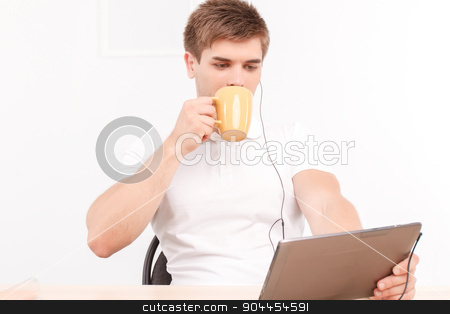 Man talking via skype on the tablet stock photo, Portrait of a handsome young man sitting at the table holding a tablet in his hands wearing earphones, drinking coffee from big cup while listening to his partner on skype talk by Zinkevych