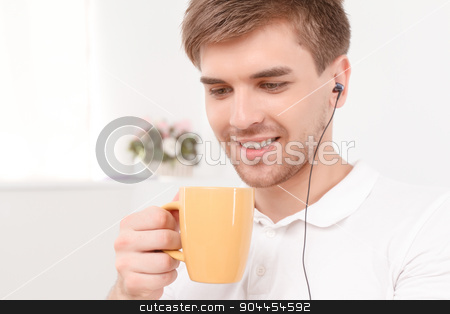 Young man drinking coffee stock photo, Close up portrait of a handsome smiling young man wearing earphones looking down and holding a yellow cup of coffee, in a light room by Zinkevych
