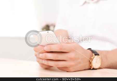 Young businessman with his smartphone stock photo, Close up photo of hands of a business man wearing watch, holding a smartphone and typing a message, wearing white polo short by Zinkevych