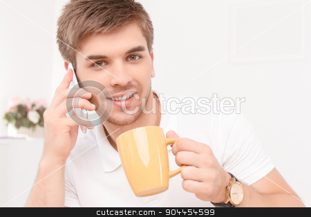 Young businessman with his smartphone stock photo, Portrait of a young handsome manager sitting in the office, talking on the phone discussing some business matters smiling, holding a yellow cup of coffee by Zinkevych