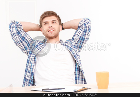 Relaxing man at the office stock photo, Young man sitting at the table in the office and relaxing, holding his arms behind his head looking satisfied, notebook and yellow cup of coffee standing on the table in front of him, selective focus by Zinkevych