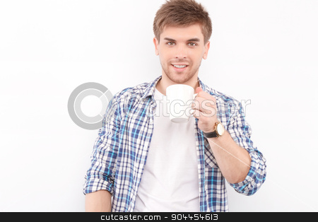 Handsome man isolated on white stock photo, Portrait of a handsome young man standing looking at the camera smiling and holding a cup of coffee in his hands preparing for drinking, isolated in white background by Zinkevych