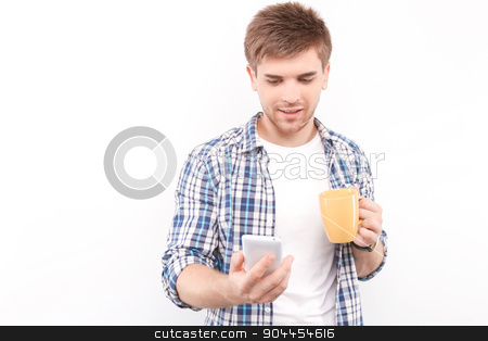 Handsome man isolated on white stock photo, Portrait of a handsome young man standing smiling and holding a cup of coffee in his hands and looking at the phone, isolated in white background by Zinkevych