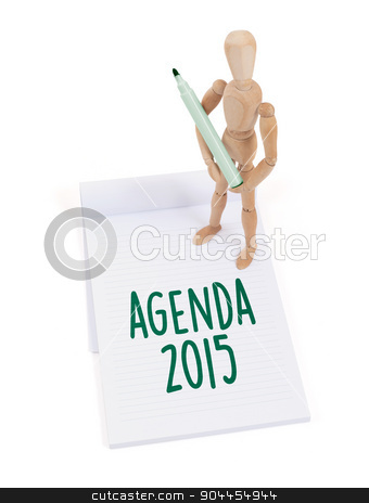 Wooden mannequin writing - Agenda 2015 stock photo, Wooden mannequin writing in a scrapbook - Agenda 2015 by michaklootwijk