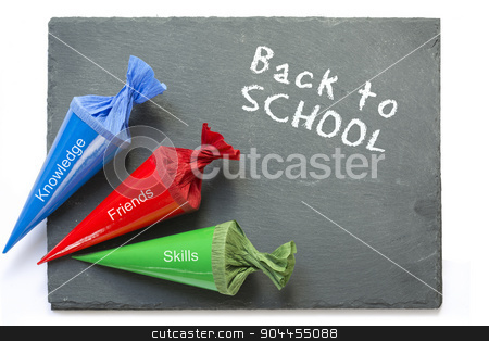 school cones on a  chartboard with message good luck stock photo, three colurful school cones with the words knowledge, friends and skills, on a chartboard with the words back to school, isolated on a white background  by Maren Winter