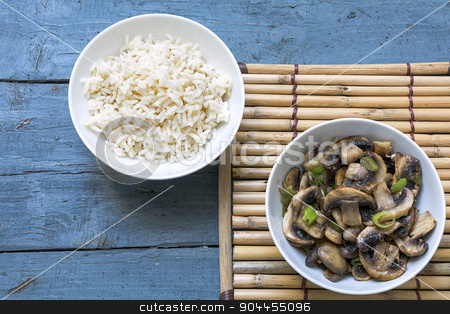 mushroom vegetables and cooked rice in bowls on a bamboo mat and stock photo, mushroom vegetables and cooked rice in porcelain bowls on a bamboo mat and rustic blue wood, view from above, copy space by Maren Winter