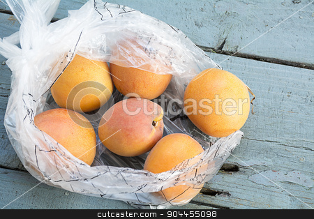 Fresh apricots in a transparent plastic bag on old blue-gray woo stock photo, apricots fresh from the market in a transparent plastic bag on old blue-gray wood by Maren Winter