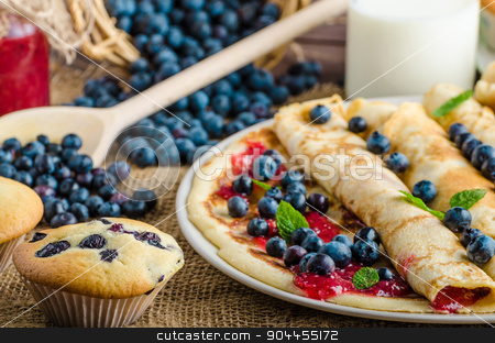 Blueberry muffins and pancakes stock photo, Blueberry muffins and pancakes, milk and jam in background and basket full of blueberries by Peteer